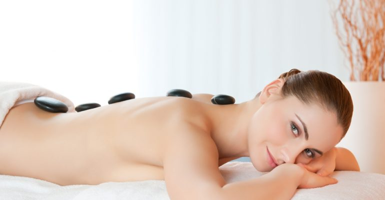 Happy smiling young woman lying with stones on back at beauty spa center